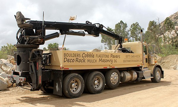 Another photo of a Southwest Boulder & Stone branded truck with attached crane used to place and position boulders