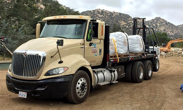 Large Southwest Boulder & Stone branded truck loaded with super-sacks and a forklift